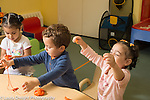 Education Preschool child care toddlers age 2, two girls and a boy playing with play dough (homemade silly putty)