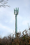 Mobile phone relay transmitter tower seen against blue cloudy sky, UK