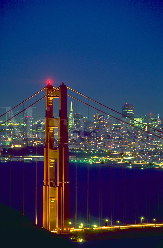 View, at night, of the San Francisco skyline lights with the Golden Gate Bridge in the foreground.