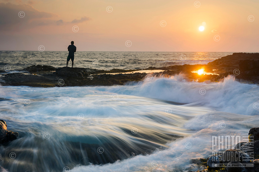A wave (in the foreground) crashes behind a fisherman on the rocky shoreline of the Big Island at sunset.