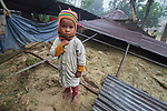 Three-year old Rittika Mardi stands in the ruins of her family's home in Suihari in northern Bangladesh. Devastating floods in August 2017 left thousands of families homeless across the region, and Christian Aid and the Christian Commission for Development Bangladesh, both members of the ACT Alliance, worked together to provide emergency food packages to vulnerable families in the affected area.<br /> <br /> Parental consent obtained.