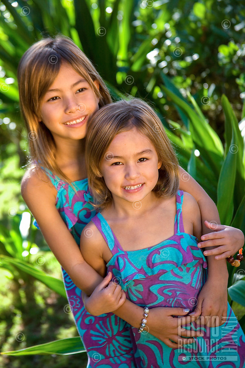 Two young sisters embrace in a garden on O'ahu.