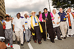 July 13, 2015. Winston Salem, North Carolina.<br />  Rev. William Barber, center, the president of the NC NAACP, leads clergy members in a march past the federal courthouse on the opening day of the NC NAACP's voting rights case against Gov. Pat McCrory.<br />  To rally support for the North Carolina NAACP's case against Gov. Pat McCrory (NC NAACP v. McCrory), a march was held in downtown Winston Salem on the opening day of the case in federal court. Thousands gathered to walk the streets of downtown and listen to speeches proclaiming the importance of defeating new requirements for voter registration,<br />  The NC NAACP contests that HB 589 (Voter ID requirements) violate Section 2 of the Voting Rights Act (42 U.S.C. 1973) and the Fourteenth and Fifteenth Amendments of the Constitution.