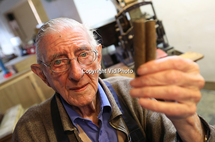 Foto: VidiPhoto<br /> <br /> KAMPEN - De oudste sigarenmaker van Nederland, de 89-jarige Martinus (Tinus) Vinke uit Kampen, hard aan het werk om een nieuwe bestelling exclusieve sigaren te produceren: met de hand. Martinus is niet alleen de oudste, maar ook de enige mannelijke sigarenroller van Nederland. Vier andere collega's zijn vrouw, een stuk jonger en opgeleid door Tinus. De 89-jarige begon als 13-jarig ventje in de sigarenfabriek Viro (Vinke Rookwaren) van zijn vader. Na zijn pensioengerechtigde leeftijd miste de hoogbejaarde sigarenman het vak enorm, waarna hij bij sigarenfabriek De Olifant uit Kampen in dienst trad voor vier dagen in de week. Alleen de exclusieve en dure sigaren, meestal op bestelling, worden nog met de hand gemaakt en dat is de verantwoordelijkheid van Tinus. Een machine produceert er 900 per uur. Tinus rolt er 600 in de week. In zijn hele leven zijn dat er naar schatting zo'n 4 miljoen. Roken doet hij overigens niet.