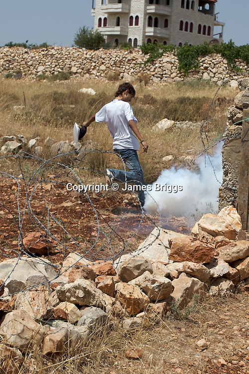 A shabab (Palestinian youth) attempts to kick away a CS gas canister fired by IDF soldiers during a demonstration in the village of Bil'in near Ramallah on 04/06/2010.