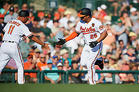 Baltimore Orioles designated hitter Anthony Santander (25) is congratulated by third base coach Jose David Flores (11) as he rounds third base after hitting a home run in the bottom of the fourth inning during a Grapefruit League Spring Training game against the Detroit Tigers on March 3, 2019 at Ed Smith Stadium in Sarasota, Florida.  Baltimore defeated Detroit 7-5.  (Mike Janes/Four Seam Images)