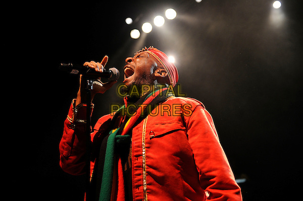 Jimmy Cliff performing in concert, Shepherd's Bush Empire, London, England.<br /> 25th June 2013<br /> on stage live gig performance music half length red orange suit tracksuit side singing hat yellow green scarf profile tracksuit<br /> CAP/MAR<br /> &copy; Martin Harris/Capital Pictures