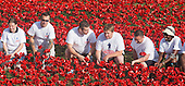 "London, UK. 30 July 2014. Volunteers from ""Coming Home"", Haig Housing's charity fundraising campaign looking at the planted flowers. A field of ceramic poppies is being planted by volunteers in the moat of the Tower of London. It will finally consist of 888,246 poppies, each representing a British or Colonial soldier fallen during the First World War."