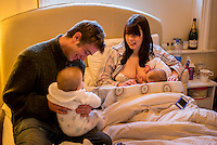 "A woman breastfeeding one of her 5 month old twins on her bed in her bedroom.  Her husband is sitting next to her with the other twin on his lap.<br /> <br /> Image from the ""We Do It In Public"" documentary photography project collection: <br />  www.breastfeedinginpublic.co.uk<br /> <br /> Hampshire, England, UK<br /> 11/02/2013"