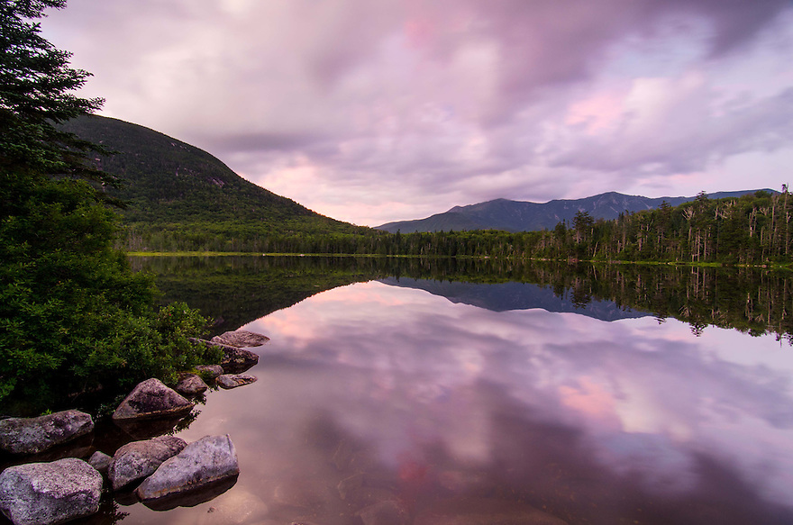 A wild purple sunset unfolds at Lonesome Lake in New Hampshires White Mountains.