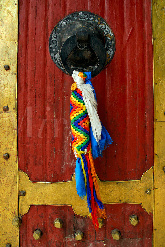 Door knocker on a west gate to the Potala Palace, decorated with multi-colored silk scarves, Lhasa, Tibet, China.
