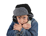 Boy freezing in the winter cold wearing woolen hat and jacket on white background