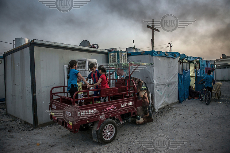 Christians displaced by ISIS militants play on a truck in an IDP camp in Erbil.