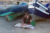 Marokko, Region Marrakesch-Tensift-El Haouz, Essaouira an der Atlantikkueste: Fischerboote vor der Medina (Altstadt), ein Fischer bietet seinen Fang zum Kauf an | Morocco, Region Marrakesh-Tensift-El Haouz, Essaouira at the Atlantic Coast: Fish seller beneath the ramparts in the fishing port