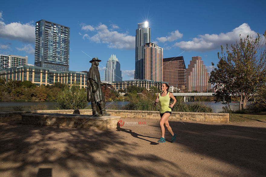 Healthy smiling female jogger runs past the Stevie Ray Vaughan Memorial Statue on the Lady Bird Lake Hike & Bike running trail with Austin skyline overset during a beautiful sunny day in downtown Austin, Texas.