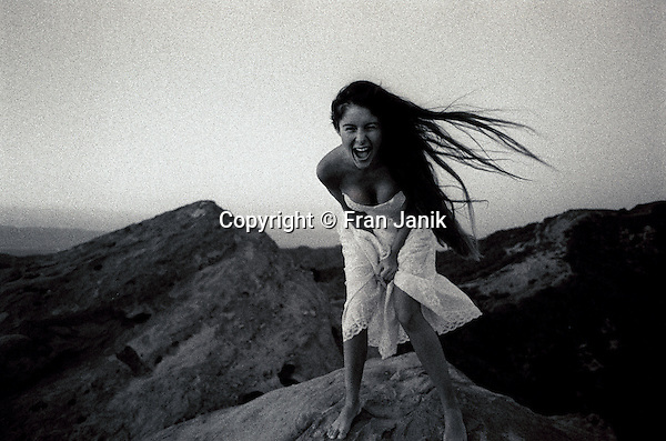 From a vantage point high in the canyons of Malibu west of  Los Angeles California, a young woman with long dark hair wearing her prom dress leans forward and yells looking into the camera. The winds picks up her hair at sunset.