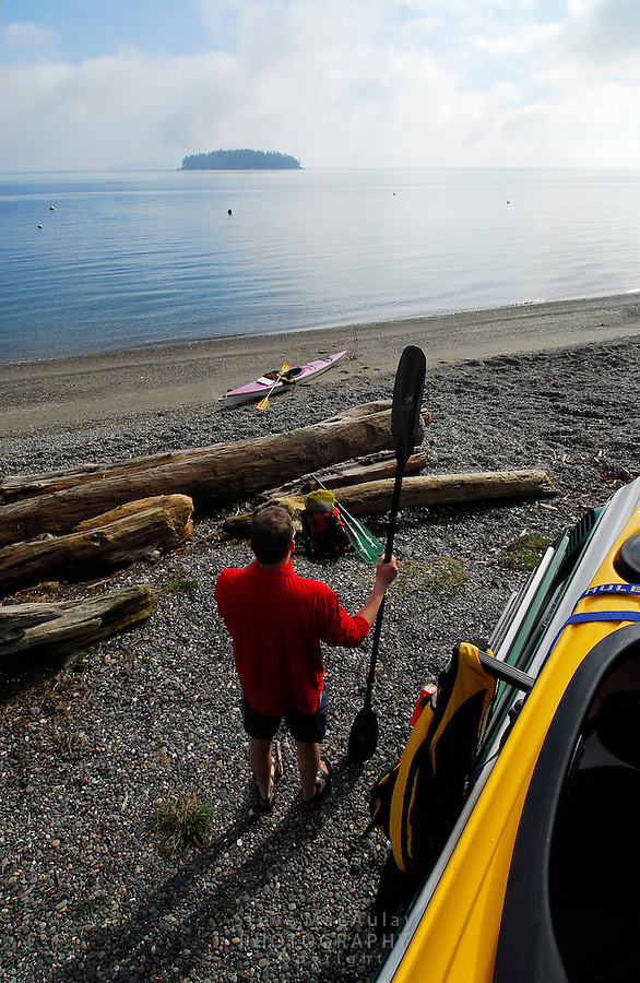 Male paddler standing with paddle on beach, with yellow and purple kayaks visible, in the San Juan Islands, Sea Kayaking the San Juan Islands, WA.