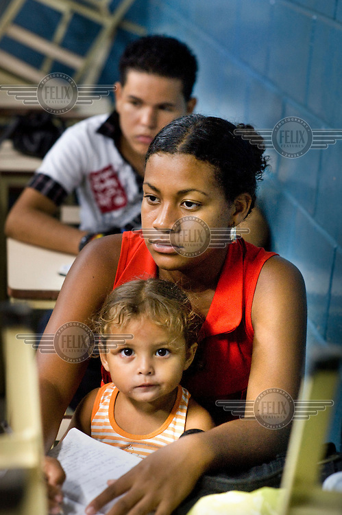 A woman, with her daughter, attends an adult education class in Puerto la Cruz run by Mision Ribas, a project funded by the the state oil company Petroleos de Venezuela.