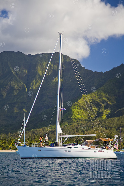 A couple on a cruising sailboat in Hanalei Bay with Namolokama Mountain in the background