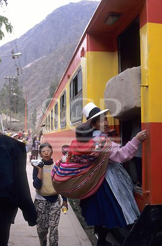 Ollantaytambo, Peru. Machu Pichu Railway - woman in traditional clothes getting on the train.