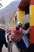Ollantaytambo, Peru. Machu Pichu Railway - woman in traditional clothes getting on the train.