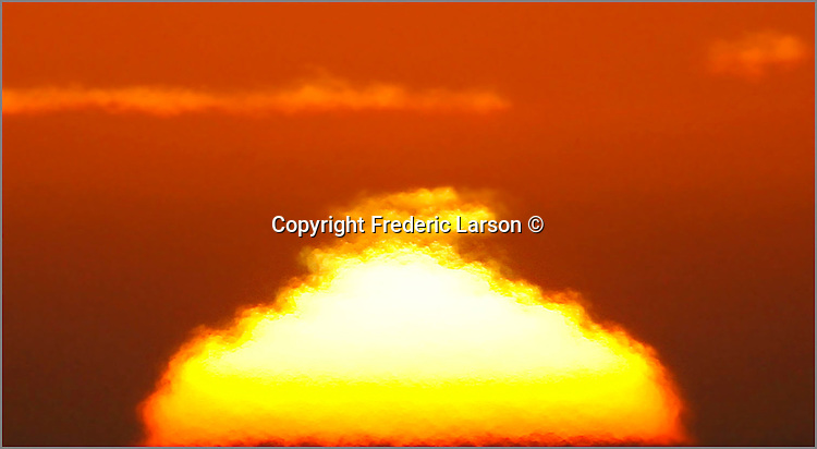The setting sun melts into the Pacific Ocean as seen from the Marin Headlands of Sausalito, California.