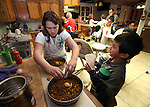LisaMarie Simon, 12, and McClain, 10, feed the family dogs at their Mound House, Nev. home, on Monday, Dec. 19, 2011. Merrill and Roberta Simon have adopted 21 special-needs children over the past 30 years..Photo by Cathleen Allison