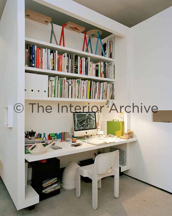 A partition screens off the office which contains a long computer table and shelving for books and works in progress