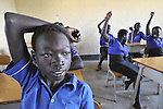 A boy raises his hand during class in a school in the Southern Sudanese village of Kenyi. The school was constructed by the United Methodist Committee on Relief (UMCOR).  Families here are rebuilding their lives after returning from refuge in Uganda in 2006 following the 2005 Comprehensive Peace Agreement between the north and south. NOTE: In July 2011, Southern Sudan became the independent country of South Sudan