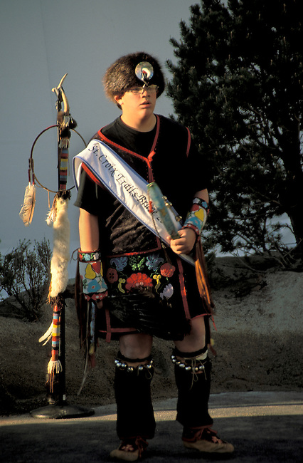 Chippewa (Ojibwa) boy aged 13-15 from St. Croix Reservation dressed in his traditional pow wow regalia of beaded apron, gloves, beaver fur cap and eagle staff or coup stick decorated with feathers, fur, beadwork and antler.