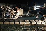 Palestinian labourers work at a cement factory at night to avoid the day time heat in Rafah in the southern Gaza Strip on June 22, 2016 during Islam's holy fasting month of Ramadan. Ramadan is sacred to Muslims because it is during that month that tradition says the Koran was revealed to the Prophet Mohammed. The fast is one of the five main religious obligations under Islam. More than 1.5 billion Muslims around the world will mark the month, during which believers abstain from eating, drinking, smoking and having sex from dawn until sunset. Photo by Abed Rahim Khatib