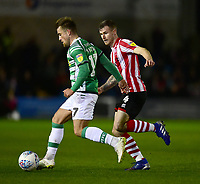 Yeovil Town's Alex Pattison shields the ball from  Lincoln City's Michael O'Connor<br /> <br /> Photographer Andrew Vaughan/CameraSport<br /> <br /> The EFL Sky Bet League Two - Lincoln City v Yeovil Town - Friday 8th March 2019 - Sincil Bank - Lincoln<br /> <br /> World Copyright © 2019 CameraSport. All rights reserved. 43 Linden Ave. Countesthorpe. Leicester. England. LE8 5PG - Tel: +44 (0) 116 277 4147 - admin@camerasport.com - www.camerasport.com