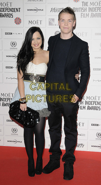 guest & Will Poulter.The 14th Moet British Independent Film Awards 2011, Old Billingsgate, London, England..December 4th, 2011.full length black dress suit white clutch bag.CAP/CAN.©Can Nguyen/Capital Pictures.