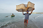 A year after Hurricane Matthew ravaged parts of Haiti, Derlien Hendy unloads a fishing net from a boat rowed by his friend Marcilien Georges off the coast of northwestern Haiti near the village of Plateforme. The village was ravaged in the storm, and Lutheran World Relief, a member of the ACT Alliance, has helped the community rebuild its economy with fishing materials, a solar-powered refrigerator room for storing their catch, and other assistance.