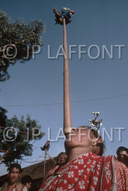 March 1979 - Child performers in a traveling circus in Haryana, India. Passersbys throw coins to a mother who balances her toddler atop a 13-foot-long pole from her chin. Child labor as seen around the world between 1979 and 1980 - Photographer Jean Pierre Laffont, touched by the suffering of child workers, chronicled their plight in 12 countries over the course of one year.  Laffont was awarded The World Press Award and Madeline Ross Award among many others for his work.