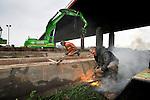 EWIJK - Langs de Waal bij Ewijk zijn medewerkers van Voorbij Funderingstechniek bezig met doorsnijden van damwanden voor de nieuwe door combinatie Waalkoppel te bouwen verkeersbrug. In opdracht van Rijkswaterstaat verrijst een nieuwe brug ten westen van de huidige die er grotendeels hetzelfde uitziet als de huidige en zich kenmerkt door vier betonnen pylonen aan de buitenzijden en tuien die het rijdek dragen. De brug is onderdeel van de wegverbreding A50 tussen Ewijk en Valburg, waarbij beide weghelften er twee rijbanen bijkregen. Omdat planken van de damwand te lang zijn om onder de brug te passen, worden ze ter plekke door midden gesneden en in twee segmenten in de grond geduwd, nadat ze halverwege weer aan elkaar gelast zijn. Combinatie Waalkoppel, bestaat uit van Mobilis, Van Gelder en Dywidag. COPYRIGHT TON BORSBOOM