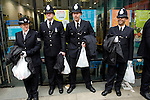 Police officers with carrier bags containing refreshments (?) on Ludgate Hill following the funeral of Margaret Thatcher, London, 17 April 2013.<br />