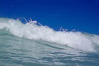 Crashing foamy waves in the blue ocean waters.