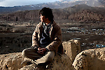 November 2012, Bamiyan, Afghanistan: Local freelance journalist Mahdy Mehraeen in a local ruin overlooking Bamiyan home to the empty Buddhas of Bamiyan niches, two 6th century monumental statues of standing buddha carved into the side of a cliff in the Bamyan valley in the Hazarajat region of central Afghanistan. .The valley is home to many Hazara's, who have often made up vast numbers of refugees to Australia, having been persecuted and driven from their homes in both Afghanistan as well as from Quetta in Pakistan where a lot of displaced Hazara fled to during the Taliban years. Bamiyan is home to a lot of Hazara who are Shia muslim and as such are looked down upon by the Sunni Pashto tribes that make up the population majority in Afghanistan.   Picture by Graham Crouch/The Australian Magazine.