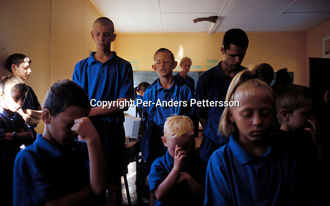 ORANIA, SOUTH AFRICA - SEPTEMBER 23: Unidentified school children prays early in the morning before classes start in the CVO, a conservative Christian school on September 23, 2003 in Orania, in the Northern Cape province, South Africa. These children are taught in Afrikaans and they have no contact with the outside world in South Africa. The village was founded in 1991 and bought by descendants of Hendrik Verwoerd, the architect of Apartheid. It?s run as a private town only accepting whites. About 600 Afrikaners lives in the village where they celebrate their culture and keep traditions alive. They have chosen not to live in today?s South Africa; a country ran by a black government since 1994..(Photo: Per-Anders Pettersson/ iAfrika Photos.....
