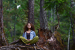 Young woman resting in a forest sitting in meditation posture leaning against a tree trunk in beautiful tranquil nature scenery