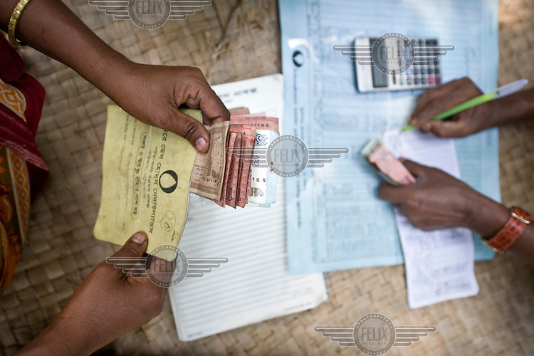An employee of the Patuakhali Development Centre who has travelled to this small village on one of the islands in the delta to receive the monthly instalments of loan re-payments and to grant new loans. This microcredit scheme was initiated by a local NGO supported by Terre des Hommes, a Dutch NGO..