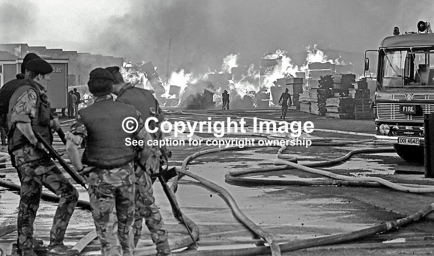 Soldiers stand guard as firemen tackle a major blaze at a timber importer's yard at Belfast docks, N Ireland, UK, on 27th June 1974. The arson attack,  by the Provisional IRA, utilised incendiary devices. 197406270367a<br />
