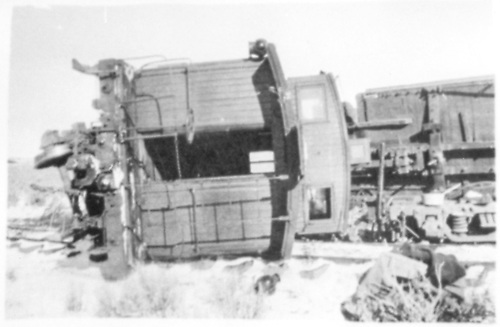 A D&amp;RGW caboose has flipped onto its side and is awaiting rescue.  Another piece of equipment is also on its side in the background.<br /> D&amp;RGW