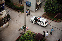 Police question a man in the courtyard of an apartment complex in Nanjing, Jiangsu Province, China.