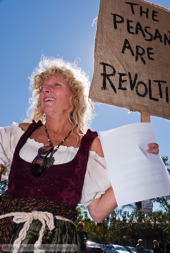 "A woman with blond curly hair holds a sign saying ""The peasants are reviling"" at the Occupy Orange County, Irvine march on November 5."