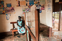 Teo Nakatudde sits in the waiting room of Bbanda Health Center, Mityana district, Uganda. In addition to government health centers there are also private health centers that many people attend since they prefer them over government health centers.