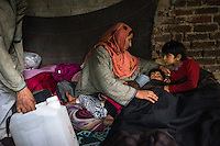 Shugufta, 29, breast-feeds Zainab, 10 months, as Azra, 5, and Igra, 8, gets ready for a nap in their temporary shelter in Narbal village, Jammu and Kashmir, India, on 24th March 2015. When the floods hit in the middle of the night, Shugufta and her family had to walk 5 miles to find shelter. Save the Children supported the family with shelter kits, blankets, hygiene items, food and tarpaulin, which they have used to build a temporary shelter next to their crumbled home. Photo by Suzanne Lee for Save the Children