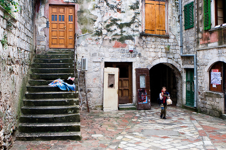 Local Montenegrin boy walking through square in Kotor's old city (stari grad), Montenegro