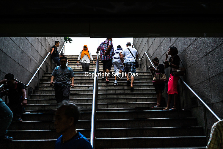 Commuters and pedestrians at the entrance of the RapidKL train station in Kuala Lumpur, Malaysia.